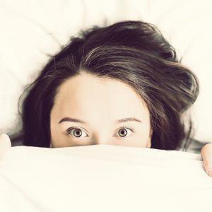 Ein Mädchen lugt unter der Bettdecke hervor