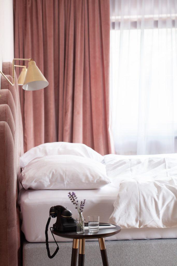 Hotelzimmer mit Retrotelefon und Rosé Samtstoffen