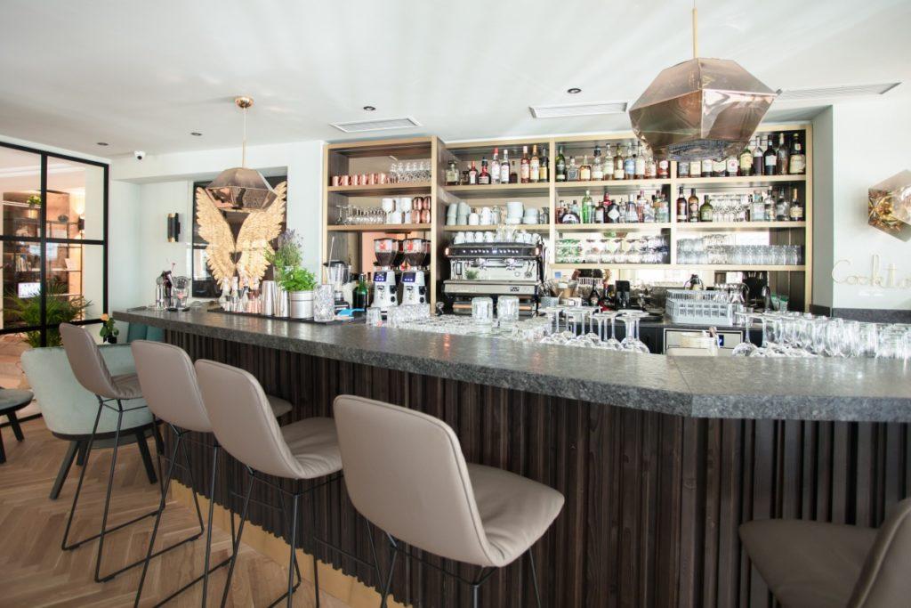 Bar mit Holzverkleidung und Stühlen davor