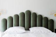 Hotelzimmer Bett mit grünem Samtende, Lampen und weißer Bettwäsche