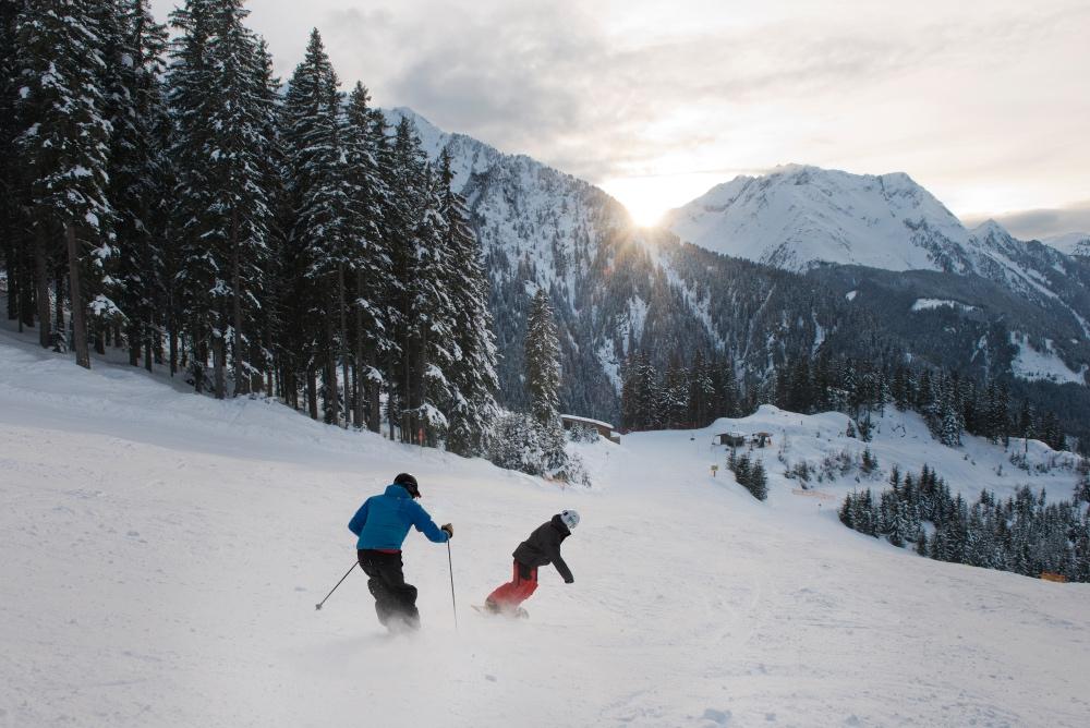 zwei Personen auf Ski und Snowboard auf der Piste mit Bäumen am Rand und Bergen im Hintergrund