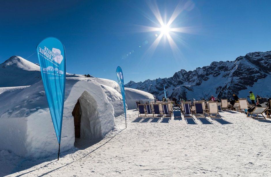 Iglu im Schnee mit Liegestühlen, Blick auf die Berge und Sonne