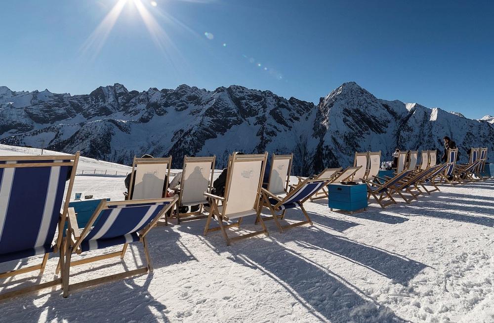 Liegestühle auf Schnee mit Sonne und Blick auf die Berge
