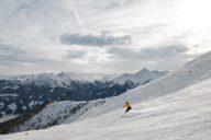 Person auf Ski auf der Piste mit Bergen im Hintergrund