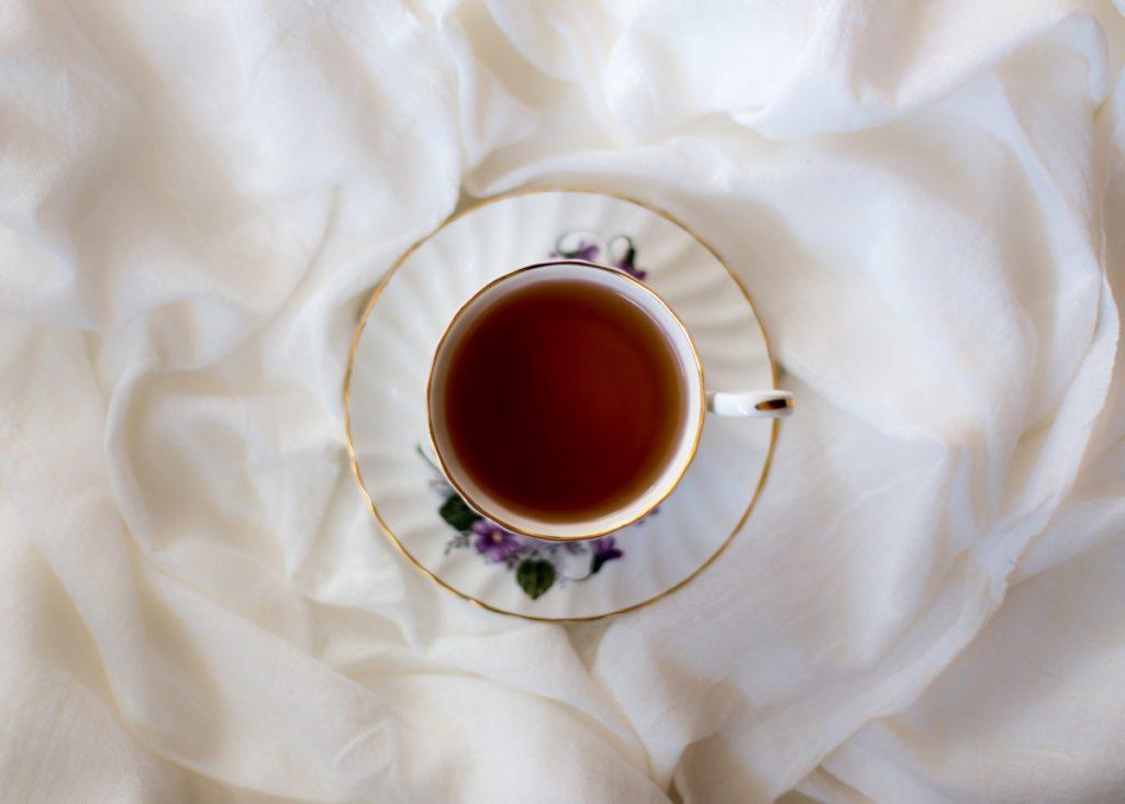 Schwarzer Tee in Tasse mit Blumen und Untertasse auf Decke
