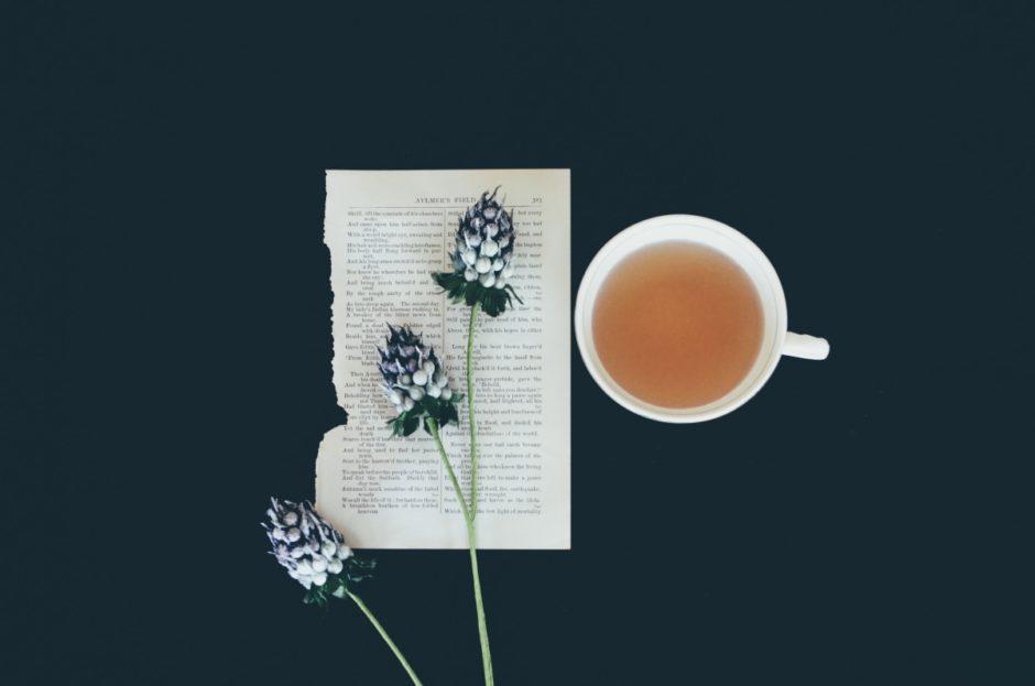 Tee in Tasse und Blatt Papier mit Blumen