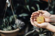 Person hält Seife in den Händen mit Text 100% handmade und Pflanzen im Hintergrund